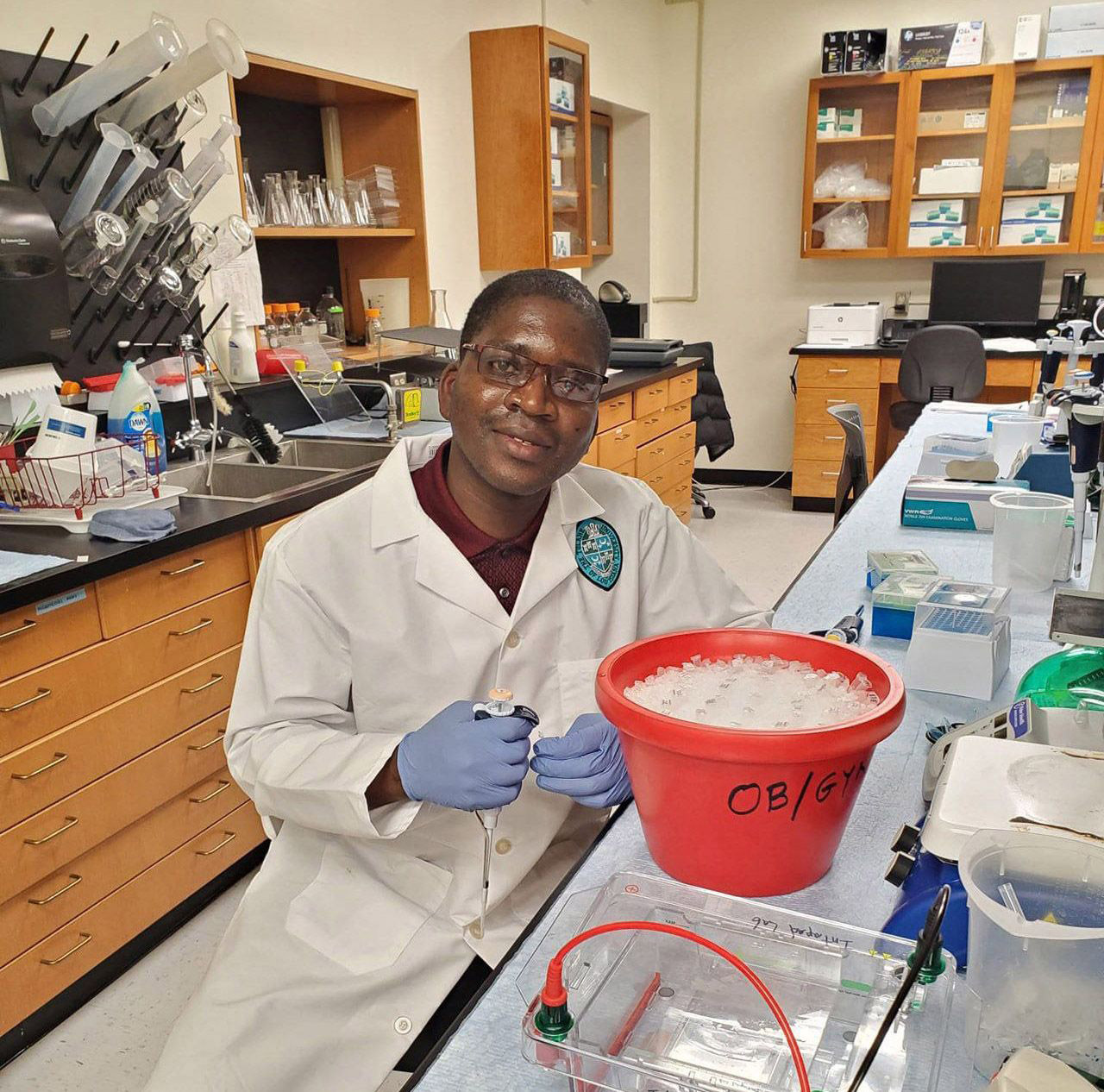 Benjamin Bhunu seated at counter in lab