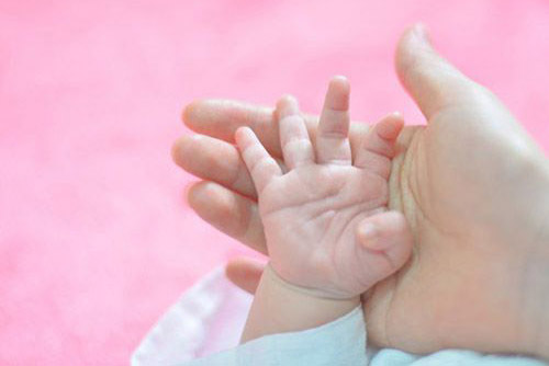 baby's hand against mother's palm