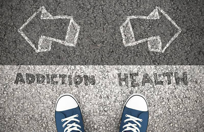 Addiction vs. Health sign with arrows pointing in opposite directions