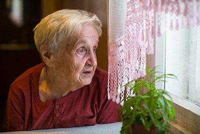 elderly woman looking out window