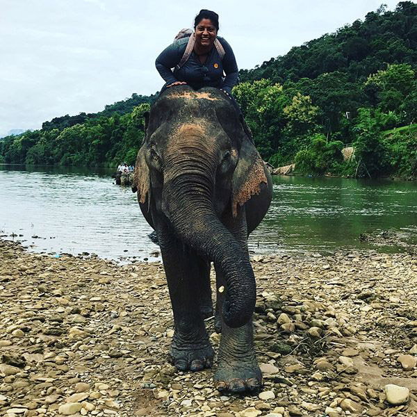 Joann Jose, MD riding an elephant